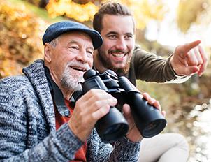 Son with senior dad looking through binoculars.